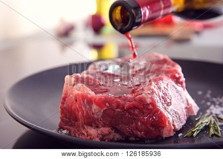 Raw pork steak with bottle of wine on black plate