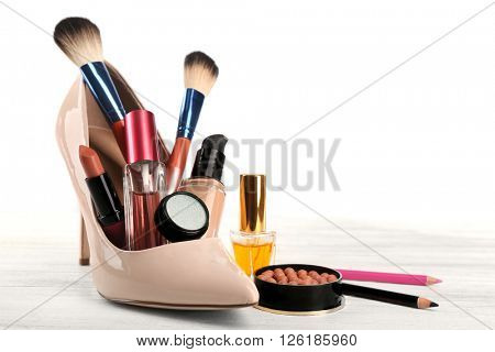 Makeup set with beige woman's shoe, brushes and cosmetics on light background