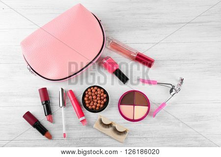 Makeup set with beautician, curler, false eyelashes and cosmetics on white wooden  background