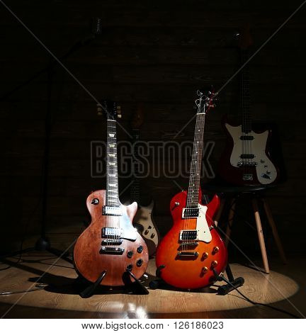 Electric guitars on lighted wooden background