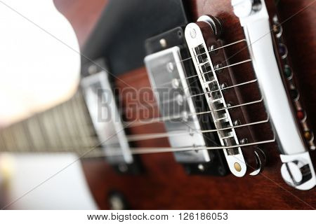Strings of brown electric guitar, close up