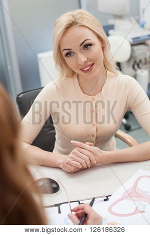 Cheerful young woman is asking advice in her gynecologist. She is sitting at the desk in hospital office and looking at the doctor with hope. The woman is smiling