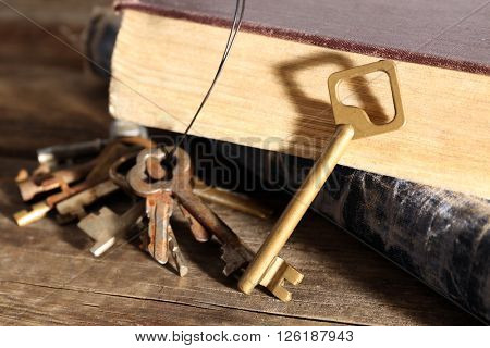 Bunch of old keys and books on wooden background