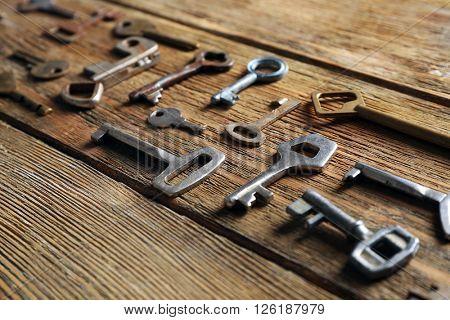 Set of different old keys on wooden background