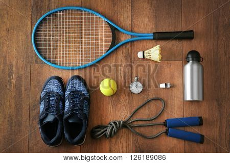 Sport equipment and footwear on wooden background