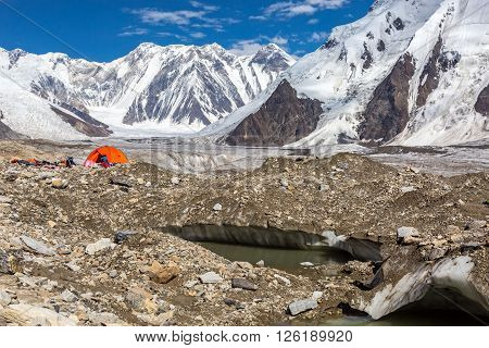Glacier Crevasse with Melting Water Lake Red Camping Tent Female Hiker and Mountain Panorama with Clean Sky and Shining Sun
