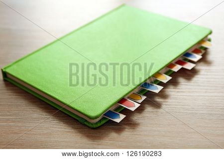 Green dairy with multicoloured stickers on wooden background