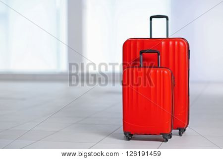 Red polycarbonate suitcases on the floor