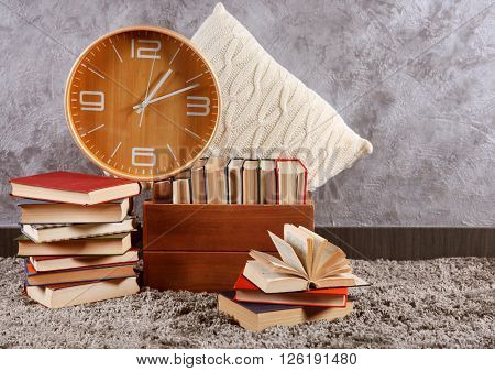 Pile of books in box and clock on wall background