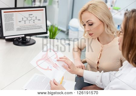 Skillful gynecologist is giving consultation to her patient. She is showing a picture of uterus to her with seriousness. The young woman is looking at paper with concentration
