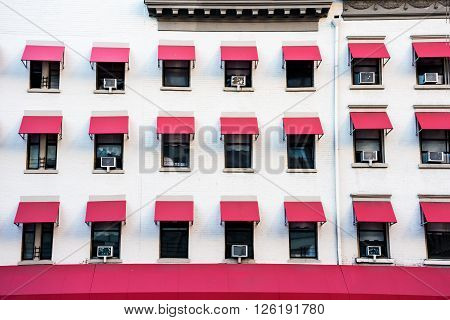 A white building with repetitive pink window shades in Manhattan. ** Note: Visible grain at 100%, best at smaller sizes
