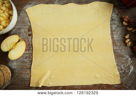 Dough for apple pie on kitchen table