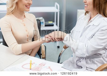 Cheerful gynecologist is supporting her patient in hospital office. She is sitting and holding her hand. Two women are smiling