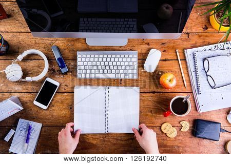 Business person working at office desk, holding a notebook. Smart phone on the table. Copy space. Flat lay.