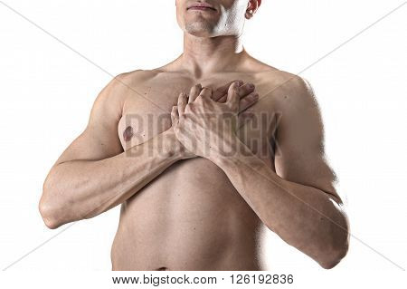 young strong body sport man with hands on his torso covering his heart in chest pain coronary problems and infarct concept isolated on white background