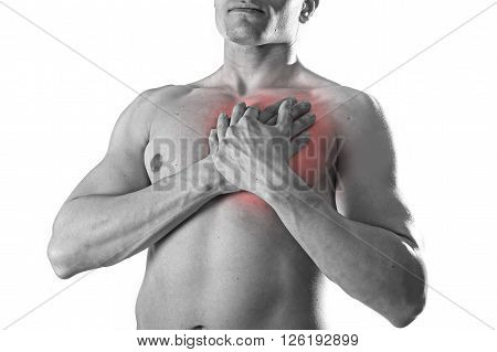 young strong body sport man with hands on his torso covering his heart in chest pain coronary problems and infarct concept isolated on black and white with red spot injury area