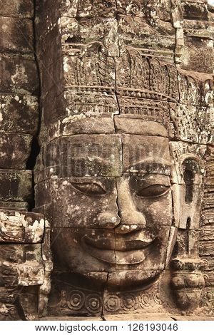 Giant stone face in Prasat Bayon Temple, famous landmark Angkor Wat complex, khmer culture, Siem Reap, Cambodia