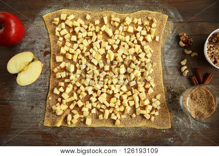Chopped apples and dough on kitchen table