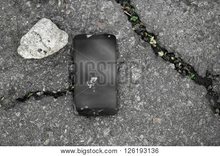 Broken mobile phone with cracked screen and stone on the pavement
