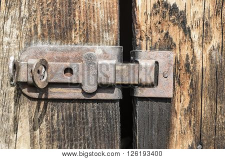 Old rusty latch on a wooden door.