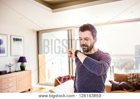 Casual hipster man working from home using smart watch, standing in living room, talking