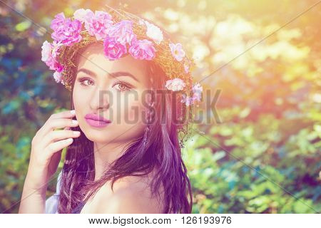Closeup beauty portrait of young brunette woman wearing makeup and pink roses wreath on her head. Soft hues, retouched, natural light.