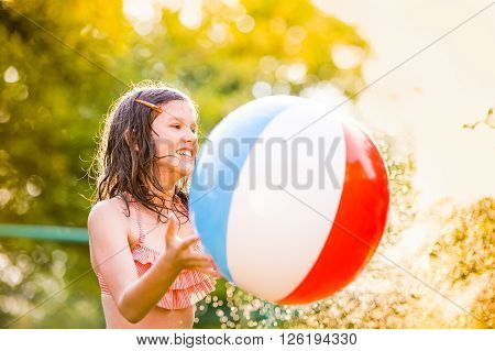 Girl in bikini with colorful ball dancing at the sprinkler, green sunny summer garden