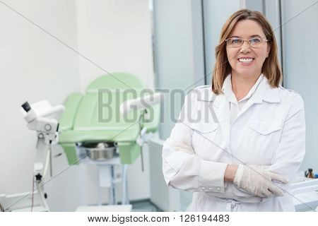 I like my work. Cheerful mature gynecologist is working in her office. She is standing and smiling. Medical chair on backgrund