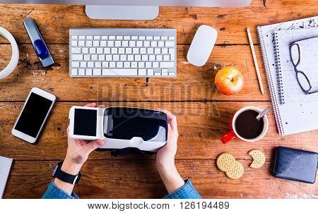 Business person working at office desk. Smart watch on hand, holding a virtual reality goggles. Various office stuff  around the workplace. Flat lay.