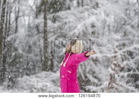 Profile view of happy young woman in bright pink winter jacket standing in snow blizzard with her arms spread widely with white snow covered trees in background.
