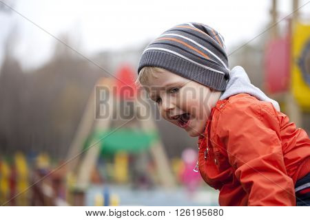 Little boy sitting on a stump in the spring park. Baby boy in orange jacket outdoors