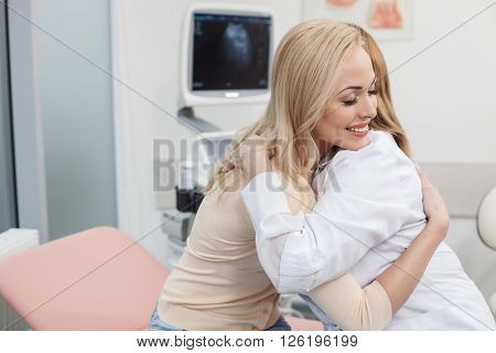 My congratulations. Professional female gynecologist is embracing her patient with joy. Young woman is sitting and smiling