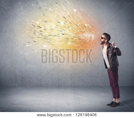 A young hipster guy with beard and sunglasses shouting in front of urban wall with vomit like colorful paint splatter on wall concept