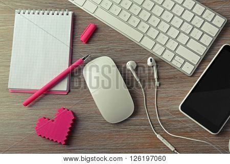 Computer peripherals with pink heart, notebook and mobile phone on wooden table