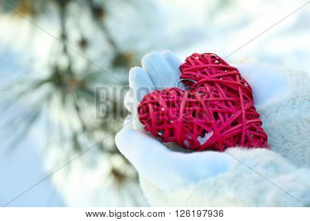 Woman hands in knitted mittens holding red heart on winter background