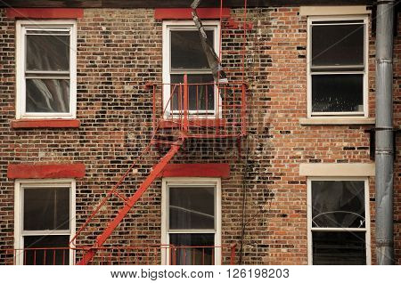 The exterior of a red brick building as a metal fire escape is located near one of the windows in New York City.