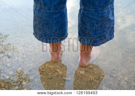 men's bare feet in the water summer day