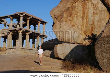 the woman examines ancient temples of the Vidzhayanagarsky era in the village of Hampi in India