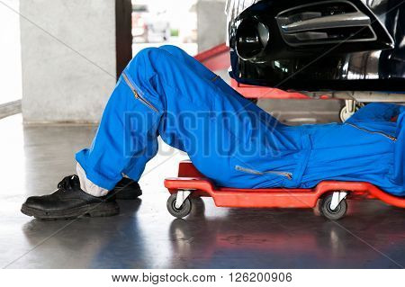 Mechanic In Blue Uniform Lying Down And Working Under Car At Auto Service Garage