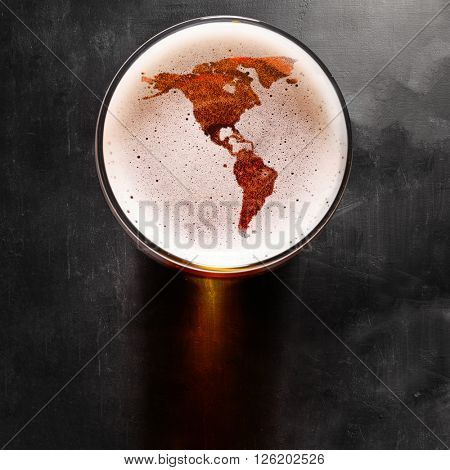 American beer concept, America silhouette on foam in beer glass on black table. The continents shapes are altered ones from visibleearth.nasa.gov