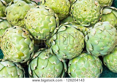 Green artichokes for sale at a market
