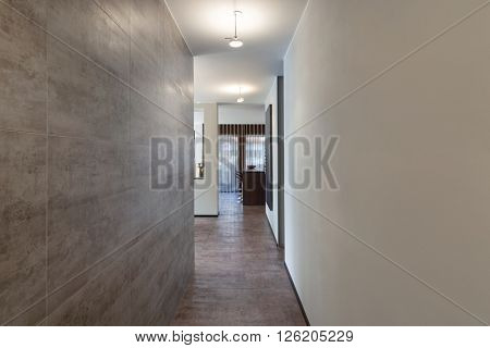 Interiors of new apartment, long corridor with marble wall