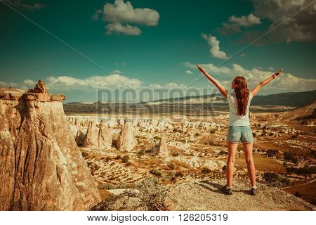 Girl standing on background of rocks formations of Cappadocia in Central Anatolia, Turkey