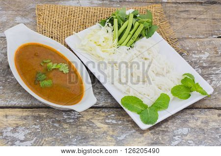 Vermicelli solution (Noodles) and fish curry coconut milk with vegetable on brown cloth background