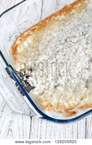 Seabass baked in sea salt on white wood background