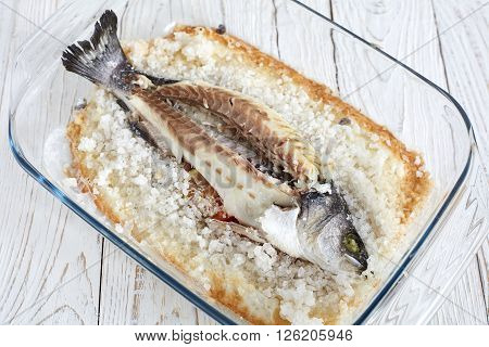 Cleaned from skin seabass baked in sea salt on white wood background