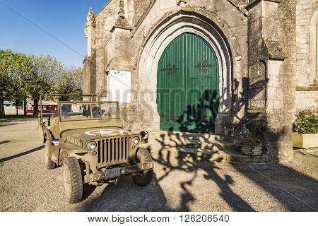 SAINTE MAIRIE DU MONT - APRIL 5, 2015: Church and American Jeep on April 5, 2015 in Sainte Marie du Mont, Manche, Normandy, France
