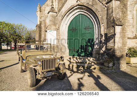 SAINTE MAIRIE DU MONT - APRIL 5, 2015: Church and American Jeep on April 5, 2015 in Sainte Marie du Mont, Manche, Normandy, France