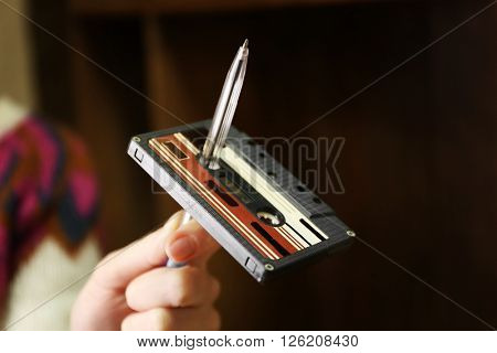 Retro cassette is twisted on pen against unfocused background
