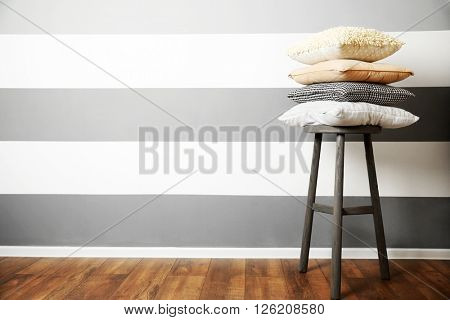 Stack of pillows on wooden stool  against striped wall background
